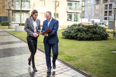 Two business people walking and discussing. Outside the office Royalty Free Stock Photography