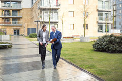 Two business people walking and discussing Royalty Free Stock Images
