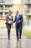 Two business people walking and discussing Stock Photo
