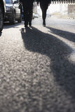 Two business people walking down a city street, long shadows on the street Stock Photos