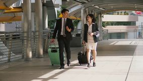 Two business people walking and drag the baggage along open pass. The businessman and pretty businesswoman walking and talking together, They are dragging a Stock Image