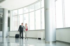 Two Business People Walking to Gate in Airport stock images
