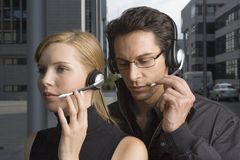 Two business people wearing headsets Stock Photography