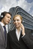 Two business people wearing headsets. Royalty Free Stock Image