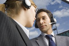 Two business people wearing headsets stand face to face. Stock Photos
