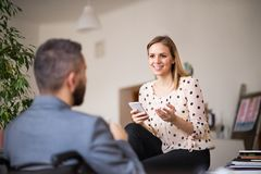 Two business people with wheelchair in the office. Royalty Free Stock Images