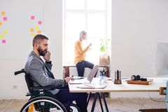 Two business people with wheelchair in the office. Stock Photography