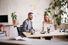 Two business people with wheelchair in the office. Royalty Free Stock Photo
