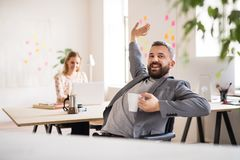 Two business people with wheelchair in the office. Royalty Free Stock Image