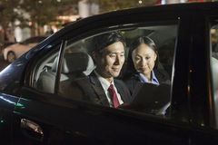 Two Business People Working In Car Back Stock Photos
