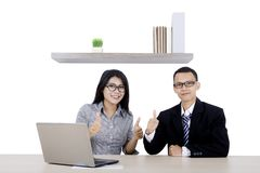Two business people with laptop and thumb up. Two business people working with a computer laptop while showing thumbs up in the office Stock Photography