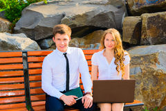 Two business people working on a laptop. Sitting on a bench in the park Stock Photo