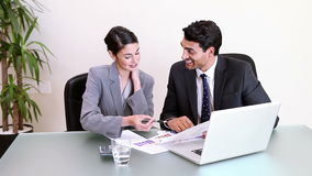 Two business people working while sitting at a desk. In a bright office stock footage