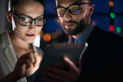 Two business people working on tablet at night stock photos