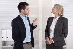 Two business people working in a team talking together in the of Stock Images