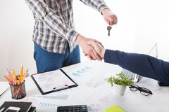 House a key in hand. Two business person shaking hands only hands to be seen and a key is be given Stock Images