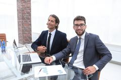 Two business person sitting behind a Desk. Photo with copy space Stock Images