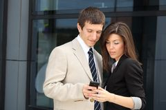Two business persons watching a mobile phone. Smiling business people when watching something funny on a smart phone Stock Photo