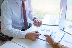 Two business point a pen to each other above chart report at meeting Stock Images