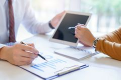 Two business point a pen to each other above tablet at meeting Stock Photo