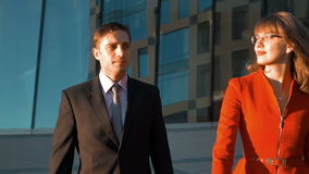 Two business smiling outdoor of the office. Two Young successful businesspeople, man in balck suit and woman in red dress and spectacles, walk near modern glass stock video