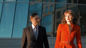 Two business smiling outdoor of the office. Two Young successful businesspeople, man in balck suit and woman in red dress and spectacles, walk near modern glass stock video footage