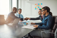 Two business teams reaching an agreement. Two young multiracial business teams reaching an agreement in negotiations stretch across the table in the conference Stock Photography