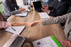 Two business teams sitting at both sides of table in meeting room. Business agreement, handshake of partners after concluding a deal. Two business teams sitting Royalty Free Stock Photography