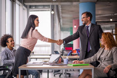 Two business teams successfully negotiating, shaking hands. At meeting table business groups shaking hands on completed deal. Man and women handshake Stock Image
