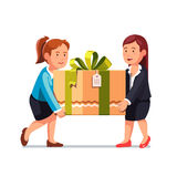 Two business woman carrying big holiday gift box Stock Photos