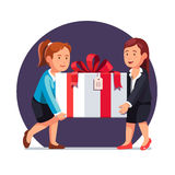 Two business woman carrying big holiday gift box Royalty Free Stock Photos