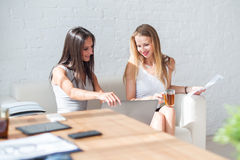 Two business woman friendly discussion during. Two business women friendly discussion during break in office using notebook and drinking coffee Royalty Free Stock Photo