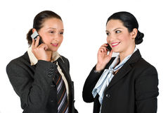 Two business woman on phone mobile. Two beautiful young business woman speaking both at cell phone and laughing isolated on white background,more photos with Stock Photos