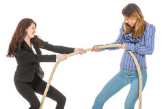 Two business woman pulling at a rope. Two business women pulling at a rope isolated at white background Royalty Free Stock Photos