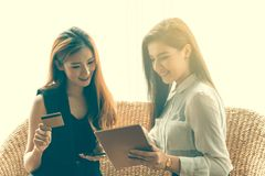 Woman Shopping Online. Two Business Woman Shopping Online by Smartphone or Tablet Pay by Cradit Card Royalty Free Stock Photos