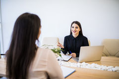 Two business woman sitting at desk: customer and adviser talking together in modern office. Two business women sitting at desk: customer and adviser talking Royalty Free Stock Image