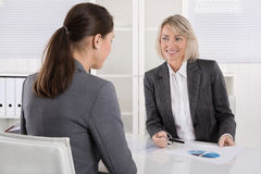 Two business woman sitting at desk: customer and adviser talking. Two business women sitting at desk: customer and adviser talking together Stock Photo