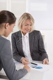 Two business woman sitting at desk: customer and adviser talking Royalty Free Stock Images