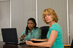 Two business woman working on a laptop computer. Two business women look forward from a laptop computer in an office conference room Royalty Free Stock Images