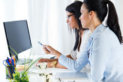 Two business woman working in office with computer. Stock Photos