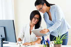 Two business woman working in office with digital tablet. Royalty Free Stock Photography