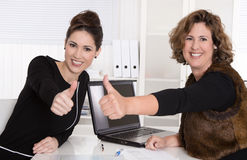 Two business woman working in a team - smiling and thumbs up. Royalty Free Stock Images