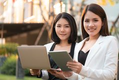 Two business woman is working together in a park outd. Two confidence business women is working together in a park outdoor stock image