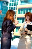 Two Business Women. Discussing their work in front of an office building Royalty Free Stock Photos