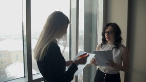 Two business women against window in hall discuss topics. Tall blonde woman with straight hair holding folder with paper, pen, listening to employee, says stock video