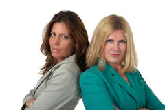Two Business Women Back to Back 1. Attractive and beautiful two business woman team standing back to back with serious expressions. Shot on white Royalty Free Stock Images