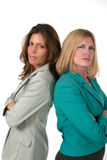 Two Business Women Back to Back 2. Attractive and beautiful two business woman team standing back to back with serious expressions. Shot on white stock photos