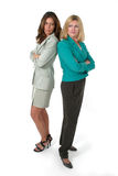 Two Business Women Back to Back. Attractive and beautiful two business woman team standing back to back with serious, glaring expressions. Shot on white royalty free stock photography