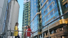 Two business women at break, talking on the street. Wide angle two business women at break, talking on the street. Background modern business center stock footage