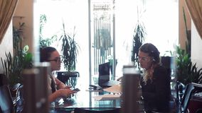 Two business women discuss a business project sitting at a table in the office opposite each other. Two business women in business clothes discussing a business stock footage